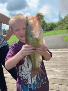 Boy proudly holds a fish he just caught.