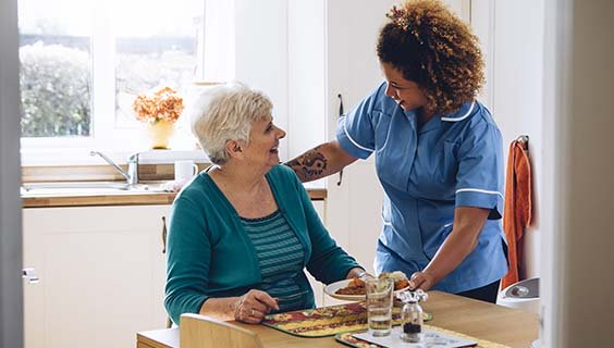 A personal aide helping a senior with dinner